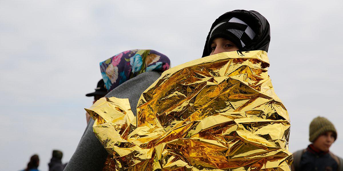 Une femme couverte par une couverture d'urgence après son arrivée en Grèce.
