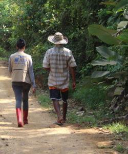 Un membre de l'équipe JRS LAC marche avec un bénéficiaire
