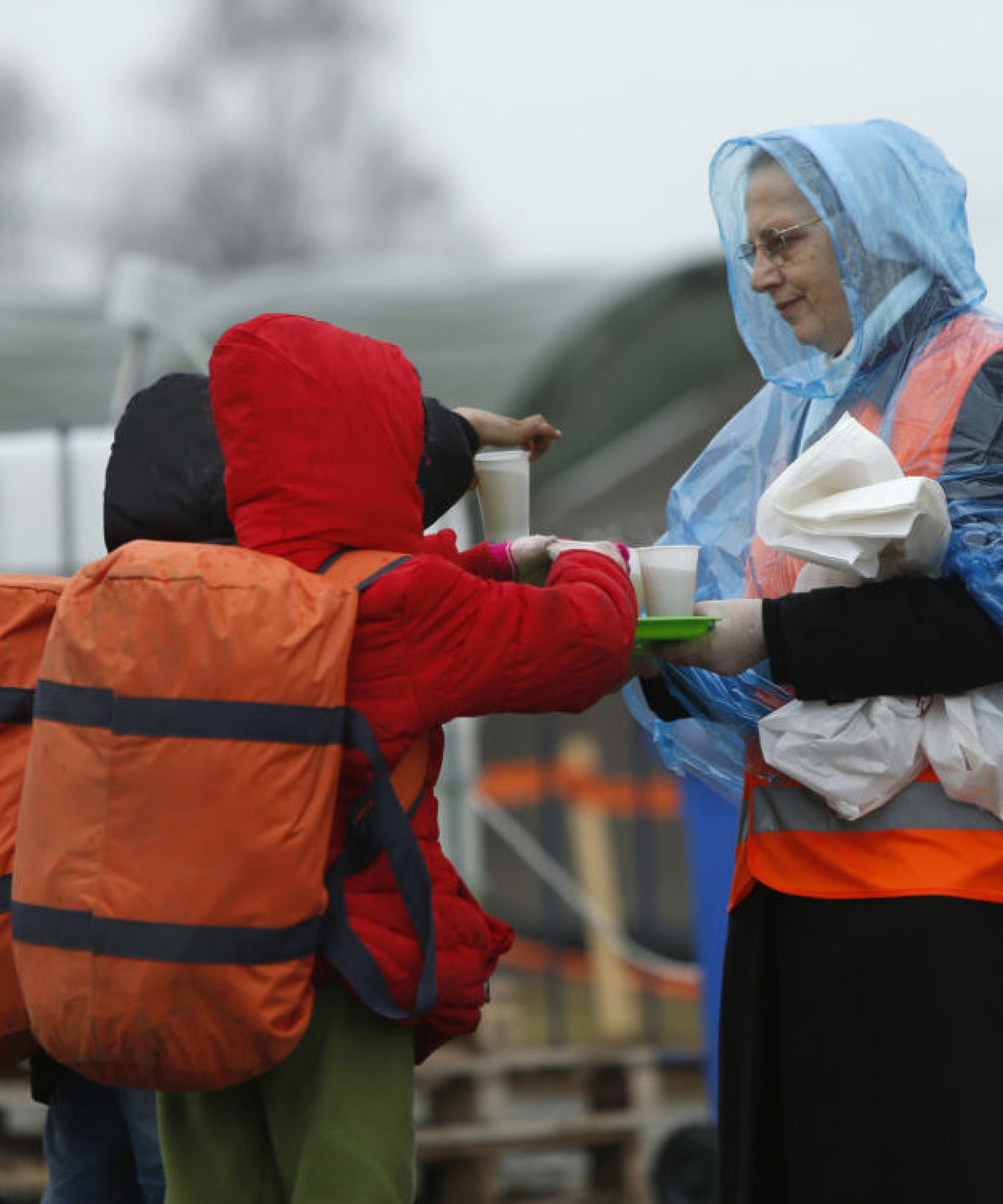 Migrant children takes cups of tea served by a nun as migrants and refugees are registered by the authorities before continuing their train journey to western Europe at a refugee transit camp in Slavonski Brod, Croatia.