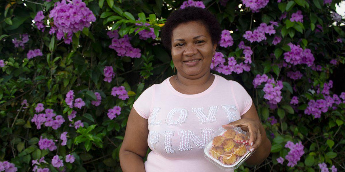 Génifer mostrando sus cocadas caseras. Ella y su amiga ahora están vendiendo un promedio de 500 cocadas por día. (Servicio Jesuita de Refugiados)