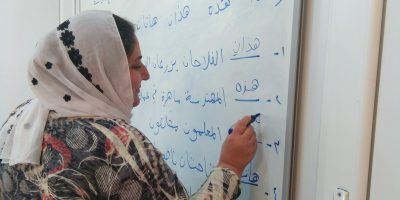 A woman practises her writing in a literacy course offered by the JRS in the Sharya Community Centre in Iraq. (Jesuit Refugee Service)