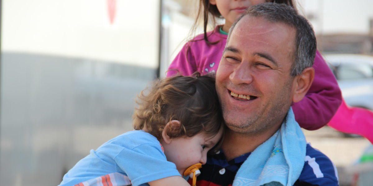 Un père iraquien passe quelques temps avec ses enfants hors de sa « maison » dans un quartier informel à Erbit (JRS)