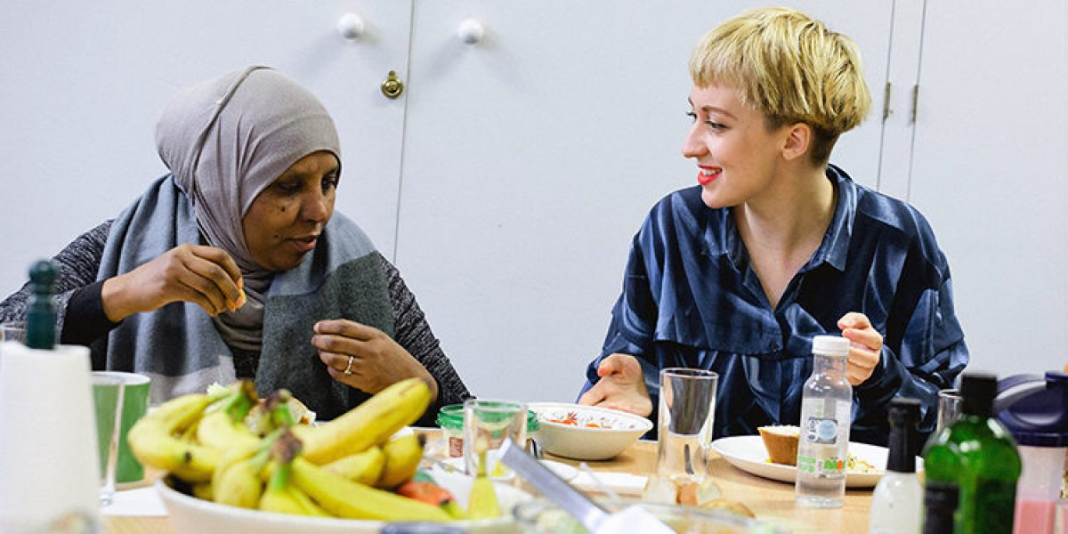 Naomi Turner, project coordinator, talks over lunch with one of the At Home guests at the JRS centre.