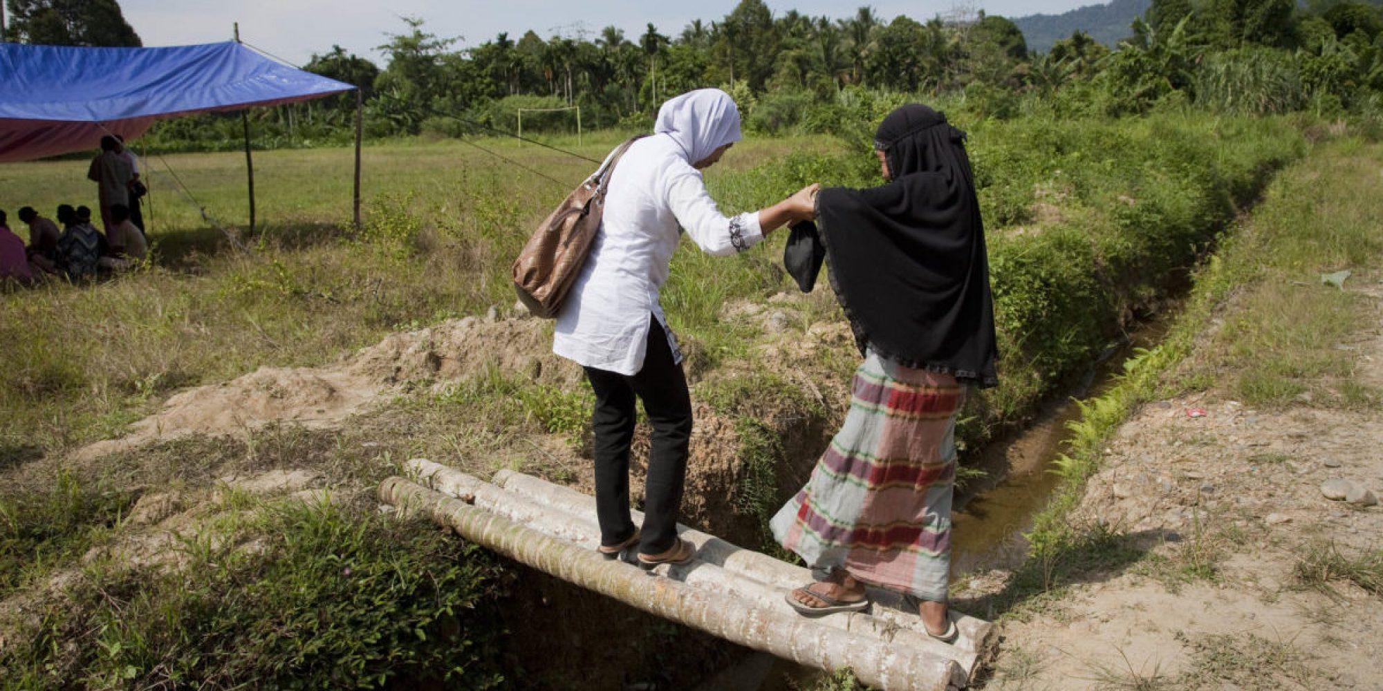 El miembro del equipo de JRS Indonesia asiste a una mujer que cruza el puente de bambú.