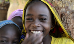 Girls smile at the JRS primary school compound in Goz Beida, Chad.