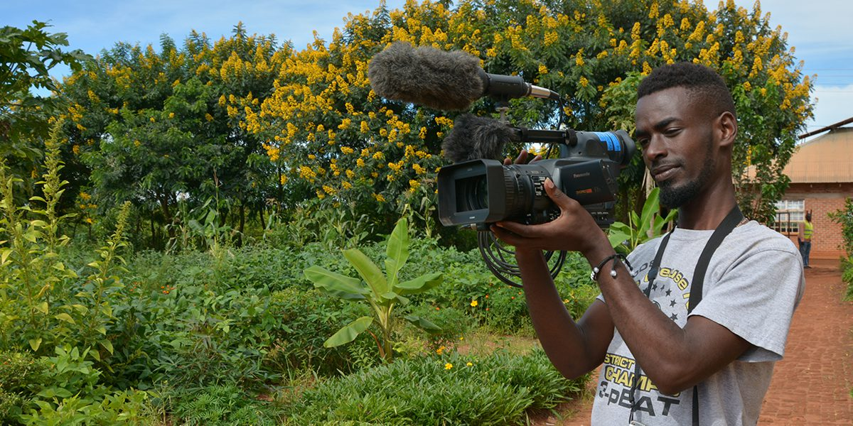 Hugo, community journalist, in action with his camera in the Dzaleka refugee camp.