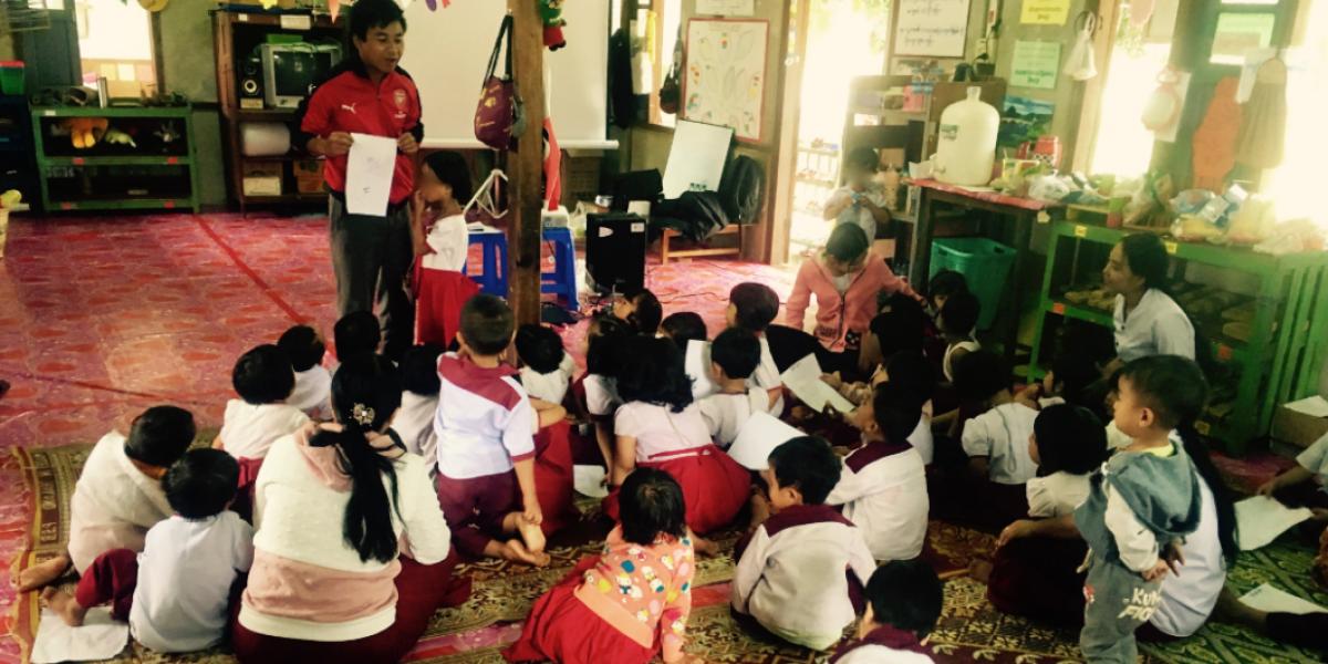 M. Mariano, responsable de l'éducation, explique un jeu d'éducation à la paix à des enfants d'école maternelle. (Service Jésuite des Réfugiés)