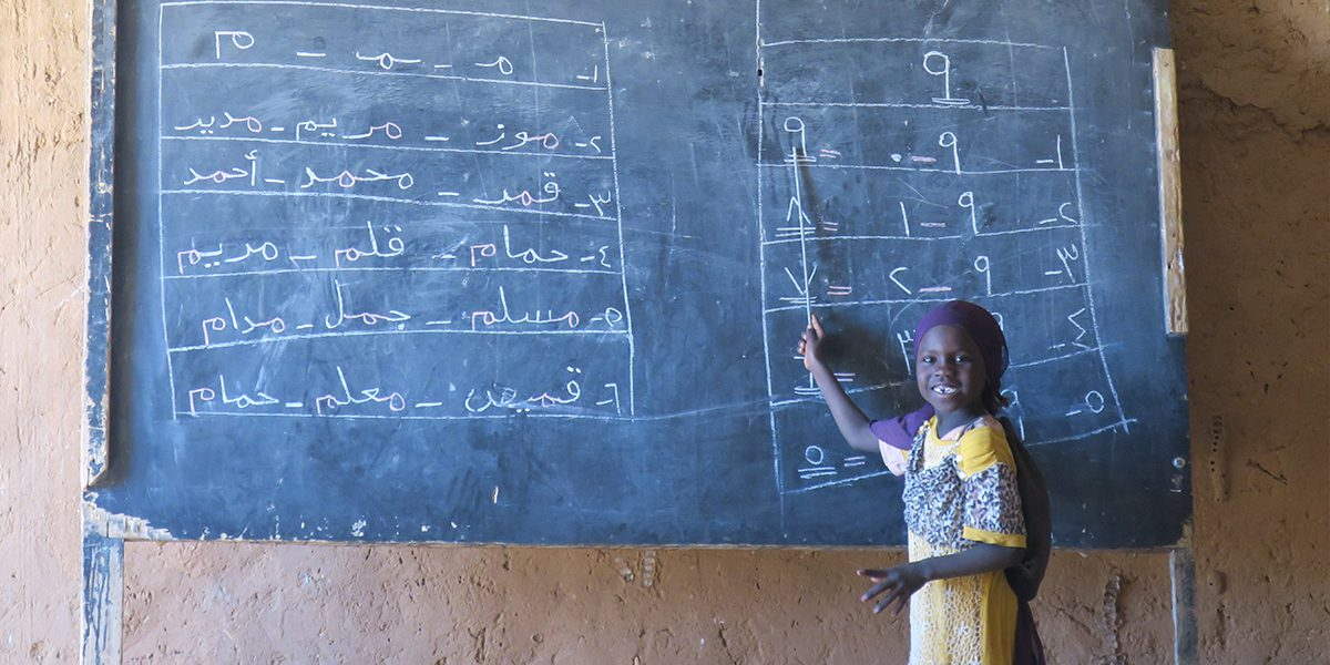 A young student learning at a primary school in Iridimi Refugee Camp.