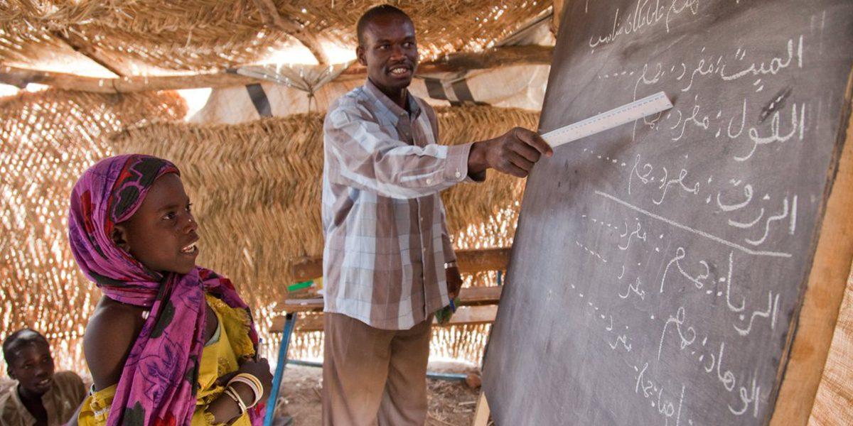 Un maestro imparte clase a sus alumnos.