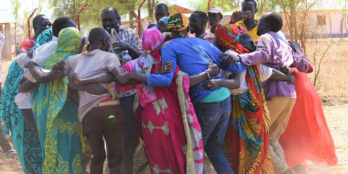 A group of adults dance, sing, and stomp their feet in a circle as they prepare for an International Women's Day celebration in Maban, South Sudan.
