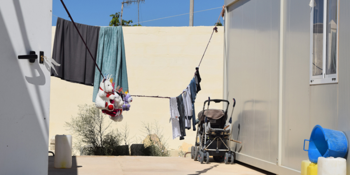 Children's soft toys hanging between container-homes at an open centre in Malta.