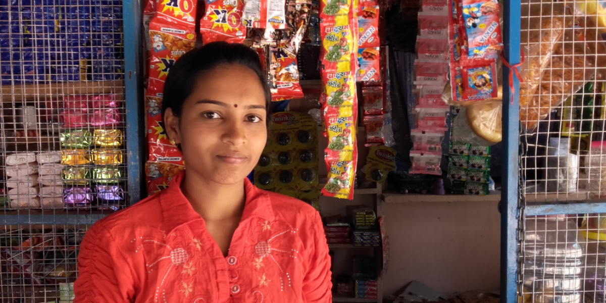 Rishna stands in front of her shop where she is able to make an income to support her family.