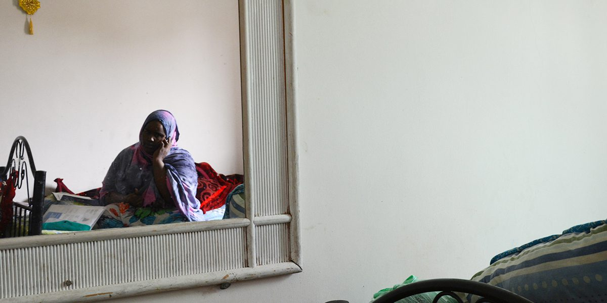A young Somali woman on the phone in her small, one-bedroom apartment in Amman.