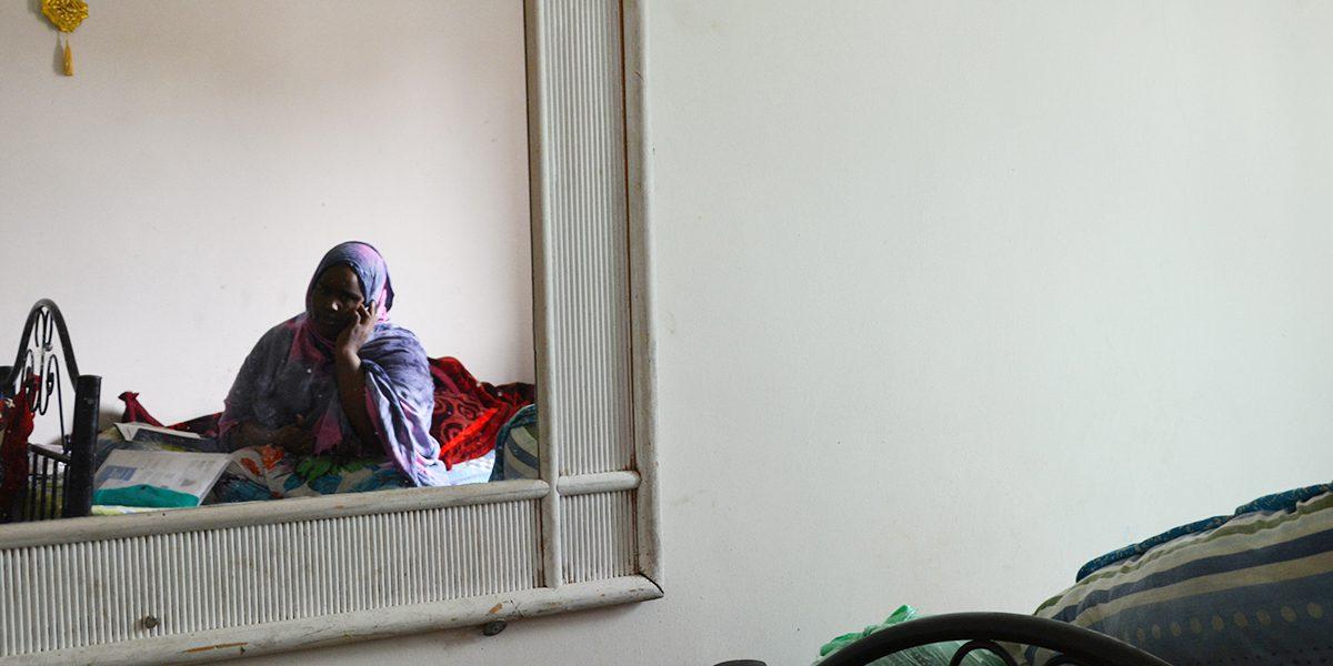 Une jeune Somalienne au téléphone dans son petit appartement, ne comprenant qu'une chambre à coucher, à Amman (JRS)