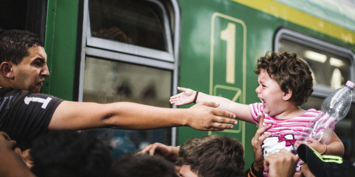 Desde un tren, este hombre, entre lágrimas y rabia, trata de tocar a su pequeño.