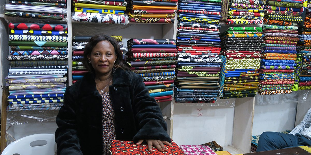Janette sitting inside of her textile store in Uganda.