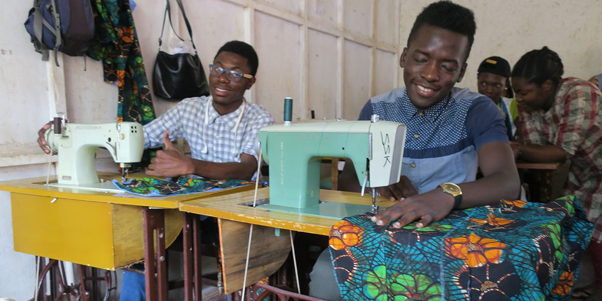 Two students work diligently in their tailoring class in JRS Kampala.
