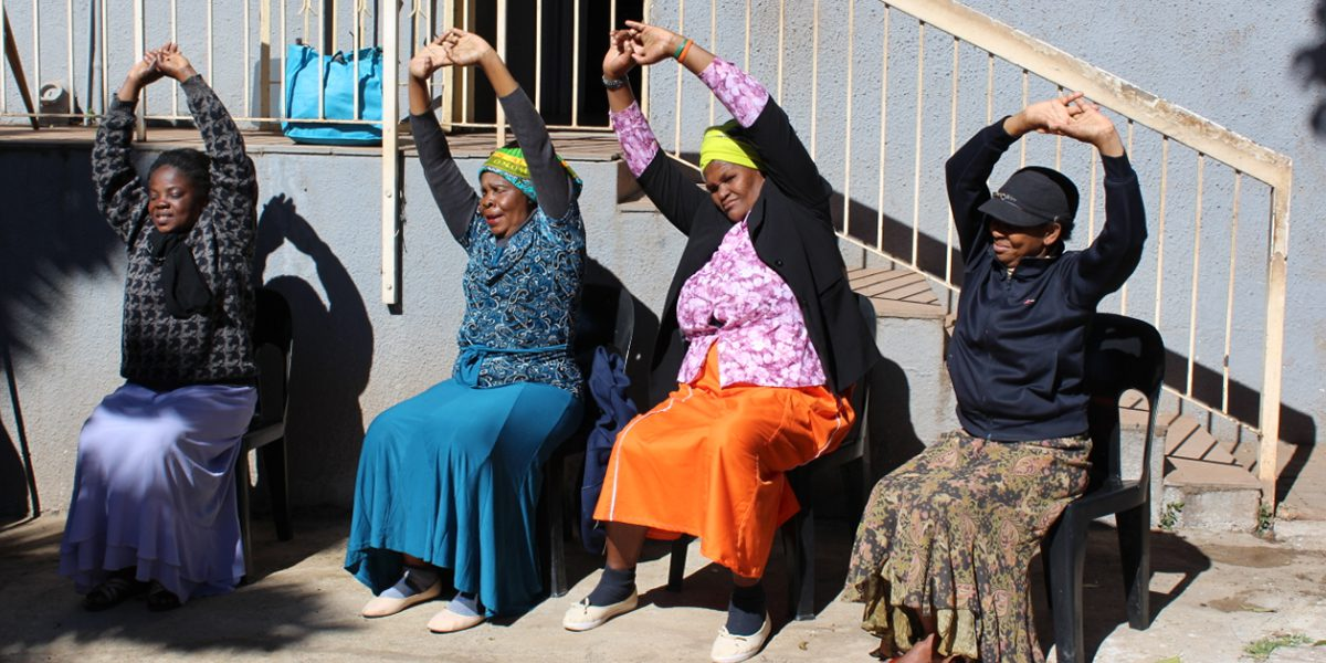 Women enrolled in the JRS South Africa Elderly Program practice yoga.