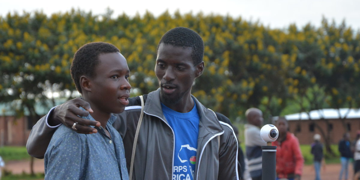 Two refugees take a break from a basketball match in Dzaleka refugee camp.