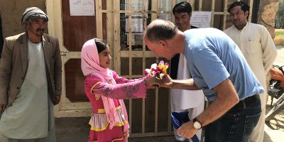 A girl welcomes Tom with flowers in Bamyam, Afghanistan. (Jesuit Refugee Service)