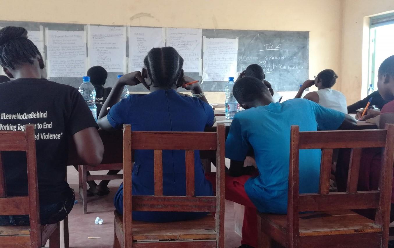 Des jeunes filles assises écoutant une classe sur les violences sexuelles et sexistes et l'estime de soi. (Service Jésuite des Réfugiés)