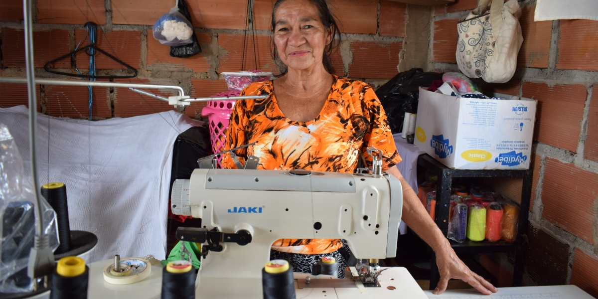 Flor Marina smiles next to her sewing machine. (Jesuit Refugee Service)