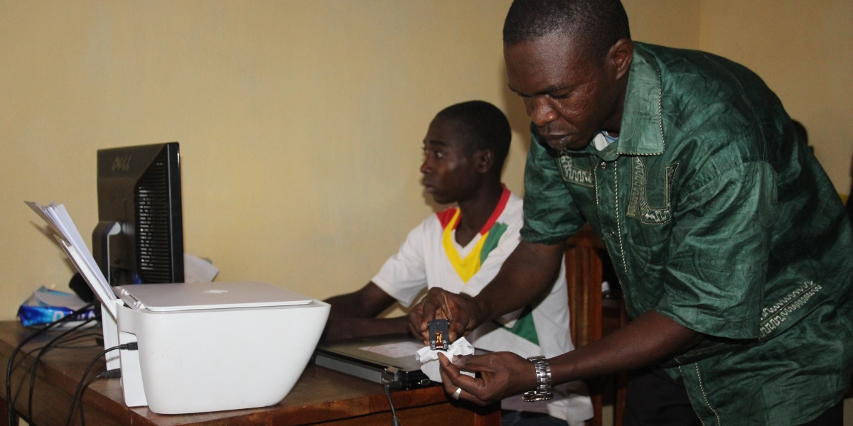 Jean Cadeau and Mahamat work hard to provide electronic services for their community. (Jesuit Refugee Service)