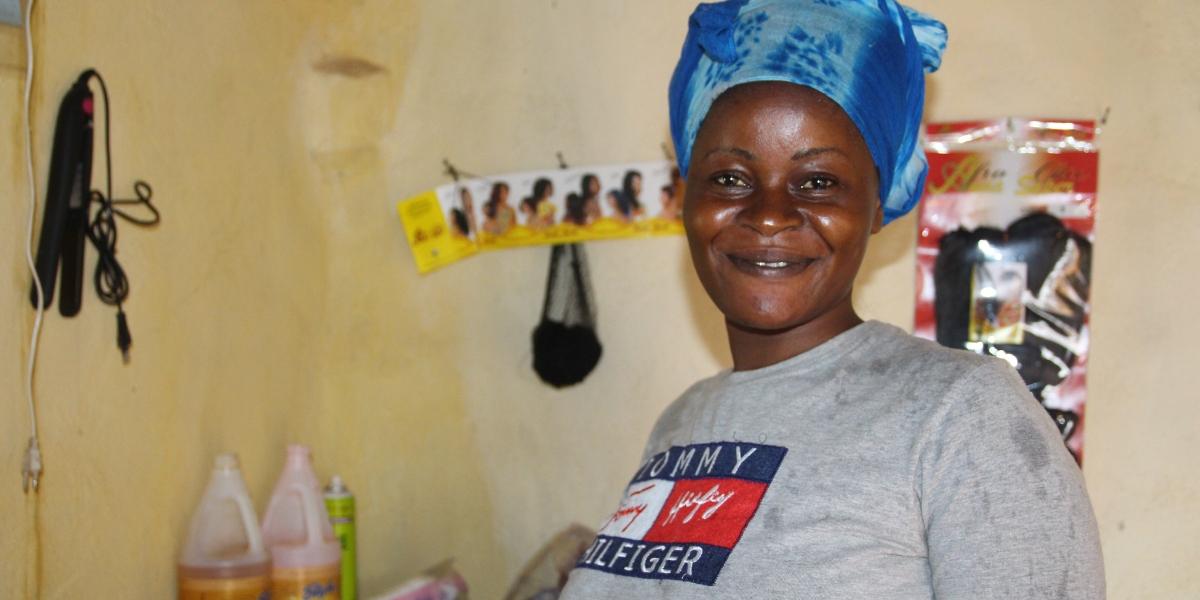 Chimene sonríe orgullosa en su salón de belleza. (Servicio Jesuita a Refugiados)