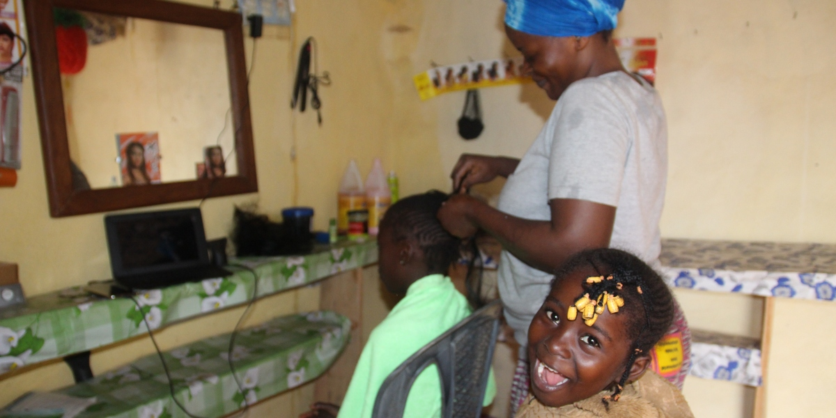 Chimene Steva works on a young girl's hair as another waits for her turn. (Jesuit Refugee Service)