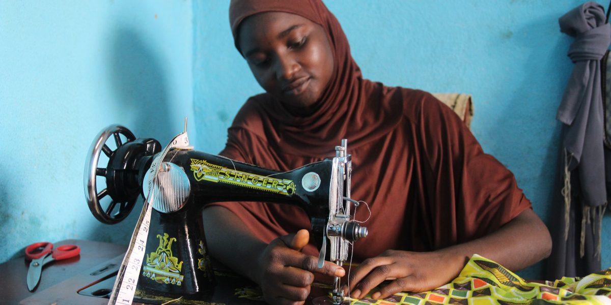 Una de las estudiantes del primer curso de costura, ofrecido por el JRS en Camerún, frente a su máquina de coser. Ella ya ha abierto su propia tienda con otras amigas del curso. (Servicio Jesuita a Refugiados)