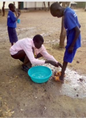A young boy is taught activities for daily living by having his feet washed. (Jesuit Refugee Service)