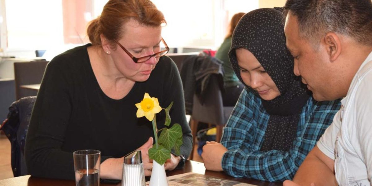 Two refugees receive language tutoring. (Jesuit Refugee Service)
