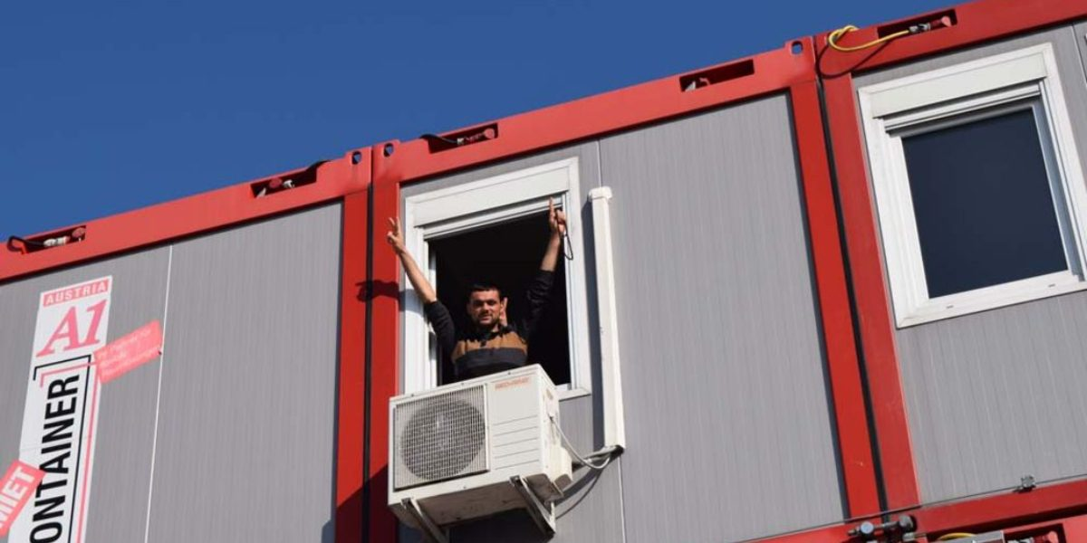 A young man gestures for peace from a shipping container home. Many refugees are accommodated in these temporary housing structures in Europe. (Jesuit Refugee Service)