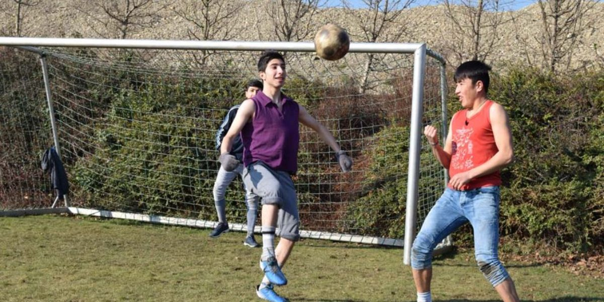 Refugees and locals play football together. (Jesuit Refugee Service)