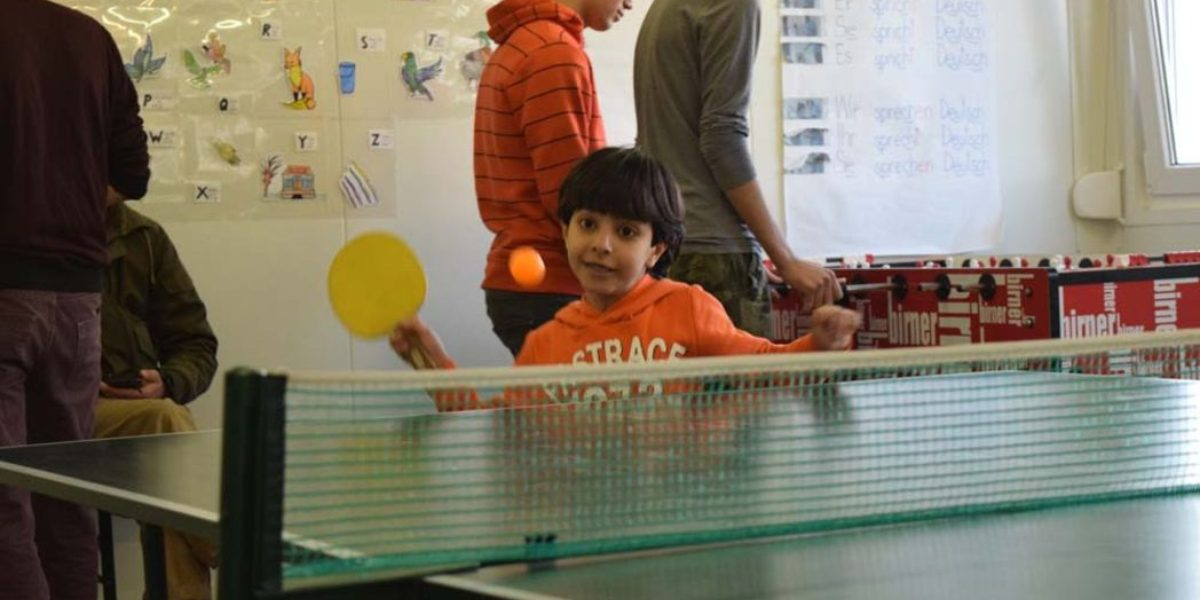 A young boy plays ping pong in a recreation centre. (Jesuit Refugee Service)