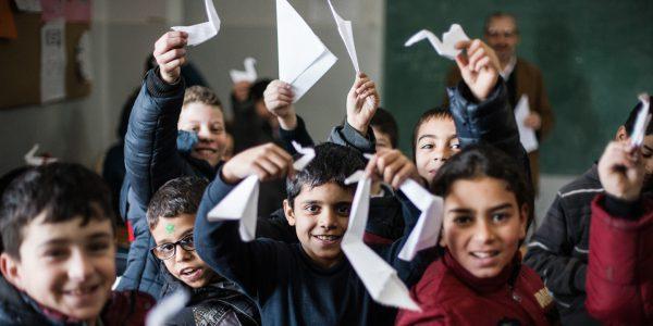 Refugee children show the work made in their art class. (Kristóf Hölvényi/Jesuit Refugee Service)