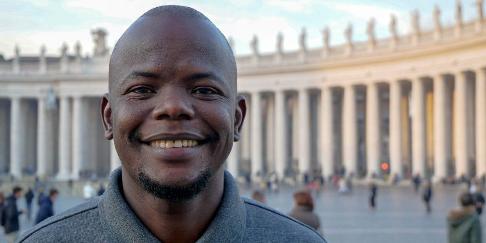 Taban Patrick Consantino SJ poses in front of St Peter's Square in the Vatican. A former JRS refugee student, Taban is now pursuing his vocation to become a Jesuit priest.