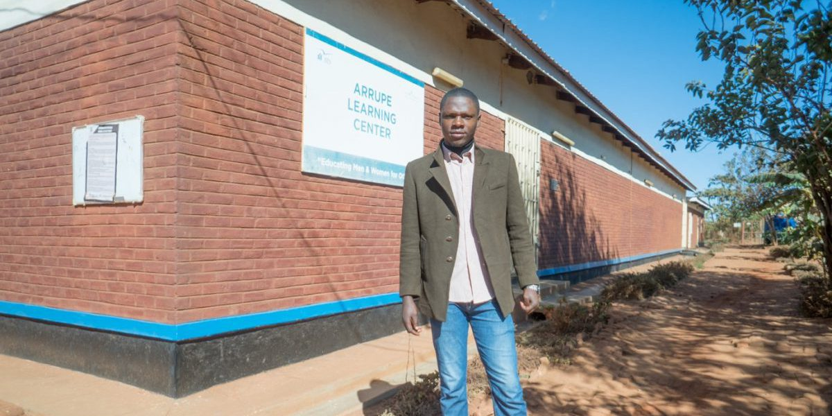Stany standing outside the Arrupe Learning Center building in Dzaleka refugee camp. (Hugo Mpenzi / JRS Community Journalist)