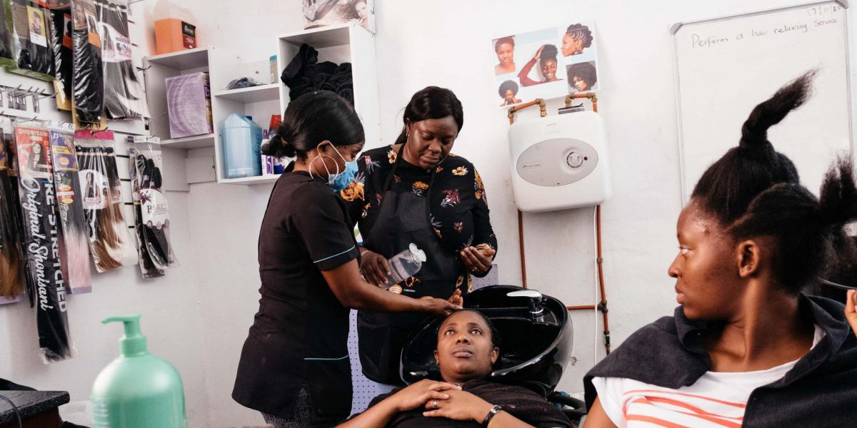 Beauty course instructor Abimbola Adeola demonstrates how to perform a hair-relaxing procedure to, from left, Mira Okito, Myriam Nkulu and Jean Dalc at the Jesuit Refugee Service's skills development centre in Pretoria. (James Puttick / New Frame)