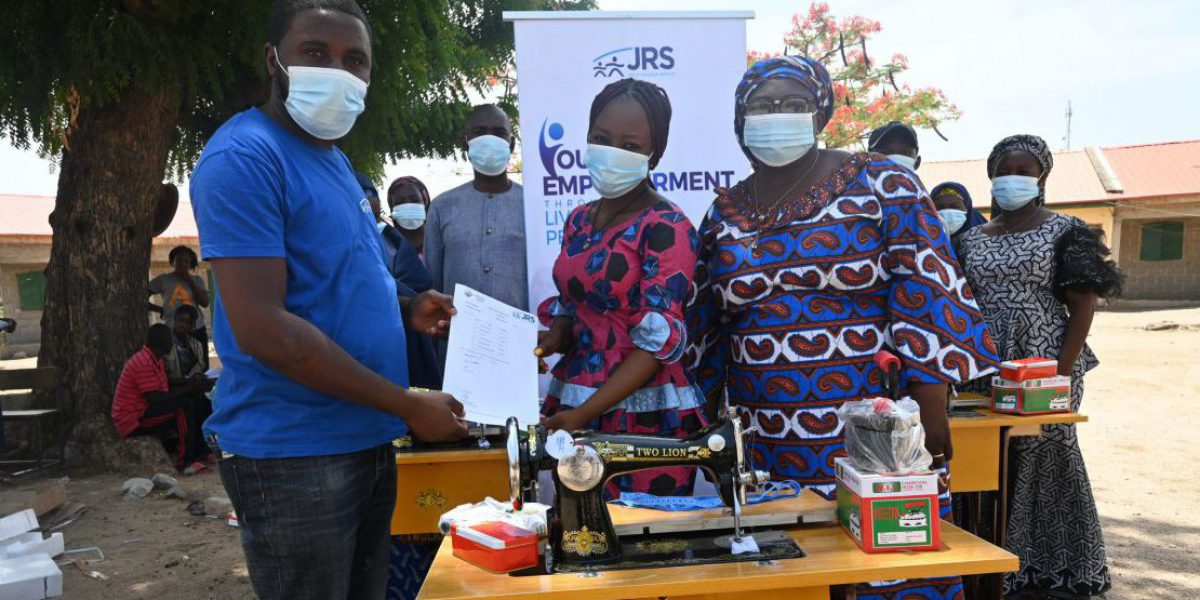 Beatrice (right) with her mother Elizbeth (left) receiving livelihood support from JRS: a sewing machine, sewing thread, a pair of scissors, a local pressing iron and a measuring tape