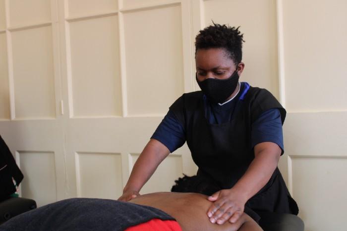 Hugette, JRS livelihoods student, demonstrating a massage technique.
